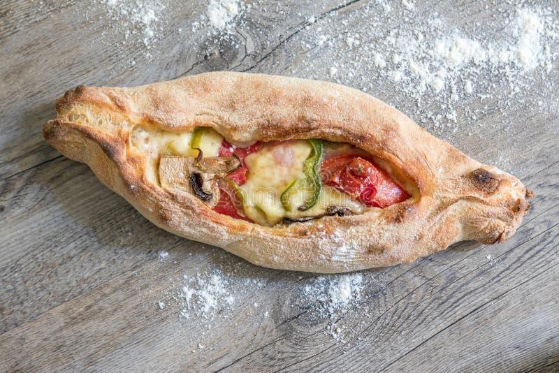 Peinirli - grecka pizza z otwartÄ… twarzÄ… z szynkÄ…, serem i warzywami wypiekana na drewnianej powierzchni kuchni fotografia stock