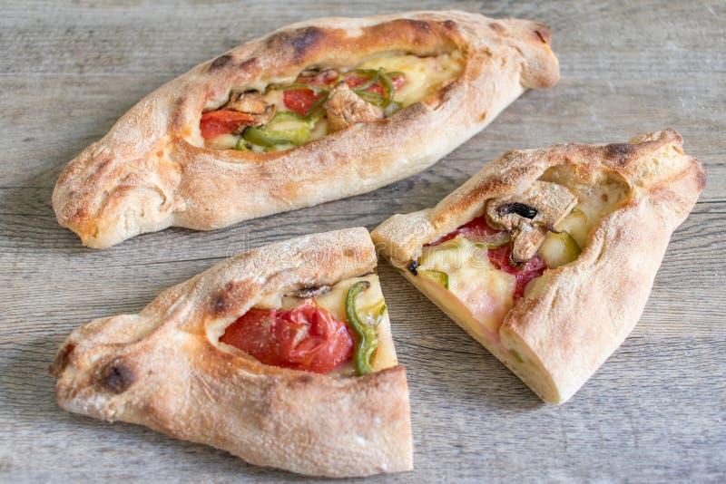 Peinirli - Griekse open onder ogen gezien pizza's met gehele ham, kaas en groenten, één en één gesneden in de helft op houten keu stock foto