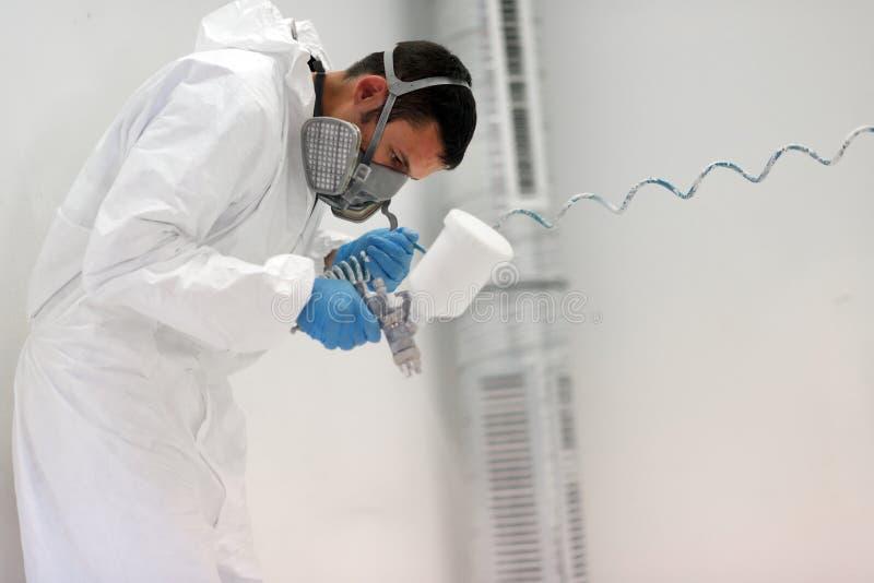 Peintre à l'aide de l'aerographe pour peindre les vêtements de protection de port photographie stock
