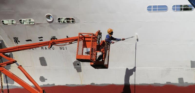 Peintre avec une coque de revêtement de rouleau de peinture d'un bateau images stock