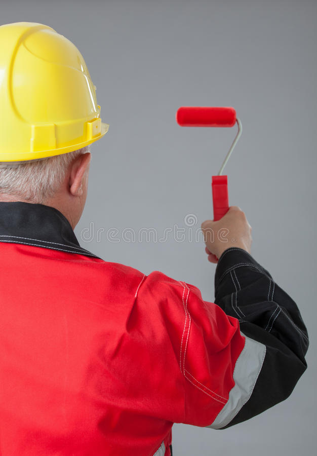 Peintre dans un casque jaune tenant un petit rouleau rouge photos libres de droits