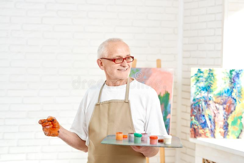 Peintre masculin supérieur, se tenant avec la palette de couleurs à disposition au studio images libres de droits