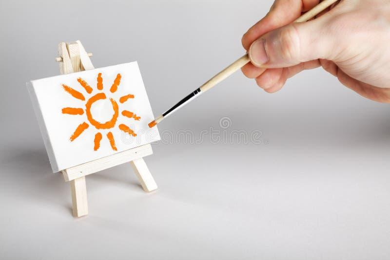 Peintre peignant un soleil sur une petite rangée image libre de droits