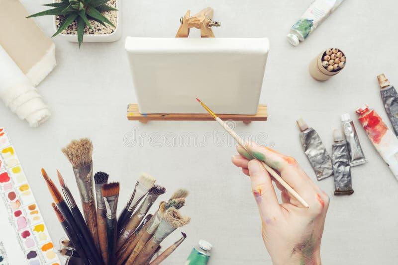 Peintre tenant un pinceau dans sa main Toile sur le chevalet et l'équipement artistique sur le bureau photographie stock