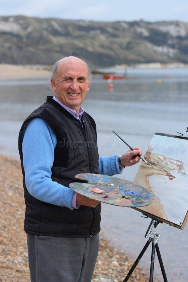 Peinture aînée d'artiste par la mer. photo stock