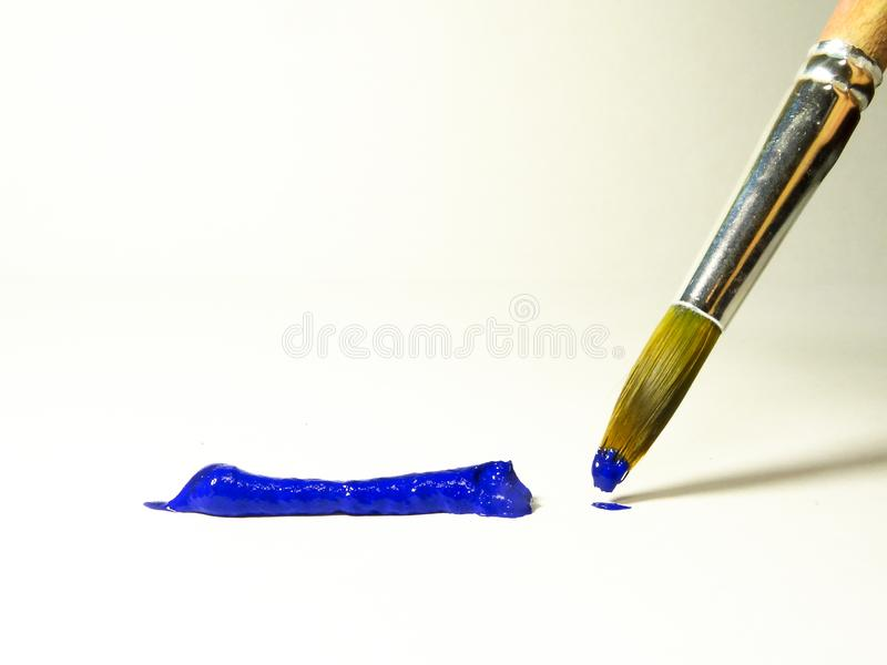 Peinture acrylique bleue sur la brosse et sur une feuille de papier photos stock