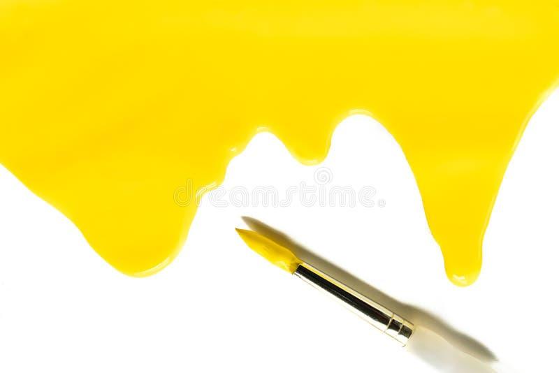 Peinture acrylique jaune lumineuse d'isolement d'égoutture avec le pinceau image libre de droits