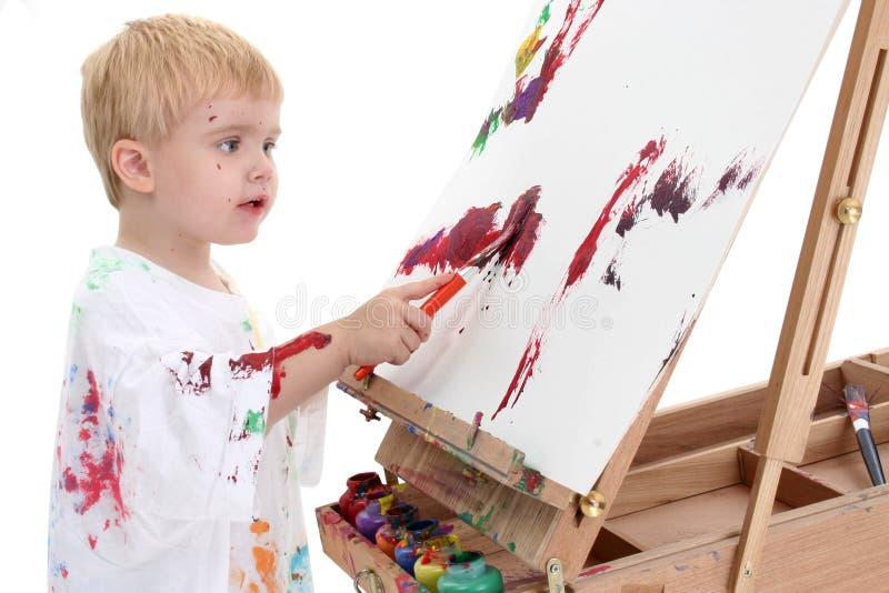 Peinture adorable de garçon d'enfant en bas âge au support photos stock