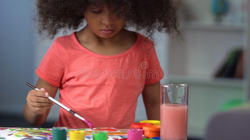 Peinture bouclée aux cheveux noirs mignonne de fille avec des aquarelles à l'école d'art, éducation photo libre de droits