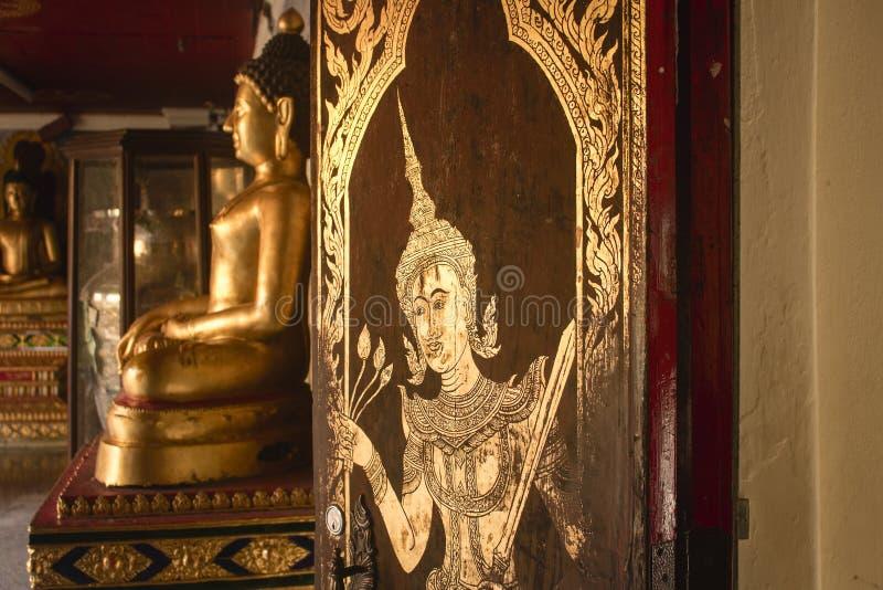 Peinture complexe de feuille d'or sur la porte de Wat Phra That Doi Suthep, avec reposer la statue d'or de Bouddha à l'arrière-pl image stock