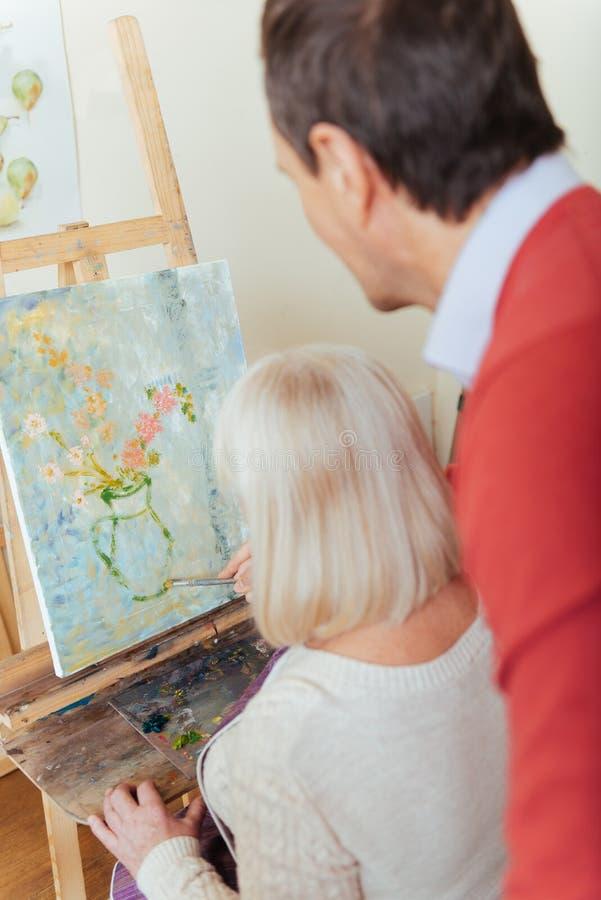 Peinture concentrée d'homme et de femme dans la classe photos libres de droits