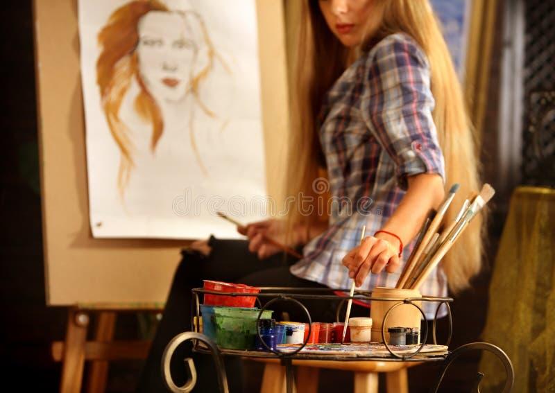Peinture d'artiste sur le chevalet dans le studio La fille peint le portrait de la femme avec la brosse photographie stock