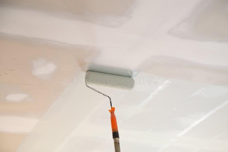 Peinture d'un plafond de plâtre de gypse avec le rouleau images stock