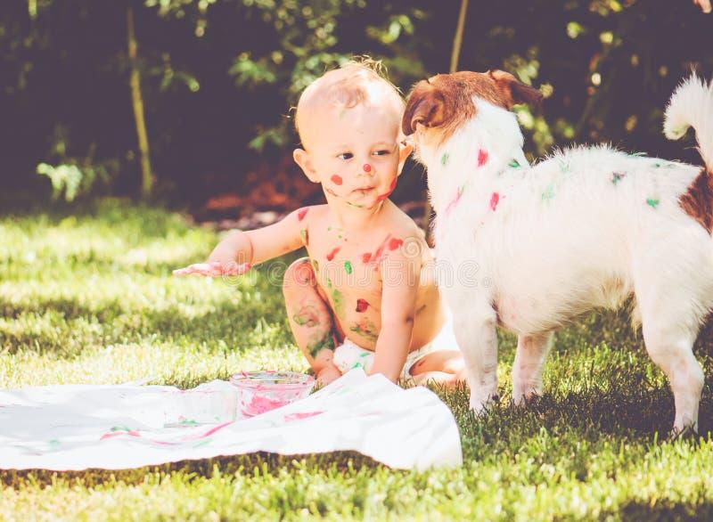 Peinture de 1 an de bébé sur son corps et sur le chien image stock