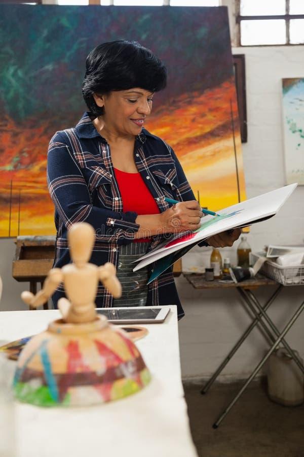 Peinture de femme dans le livre de dessin image libre de droits