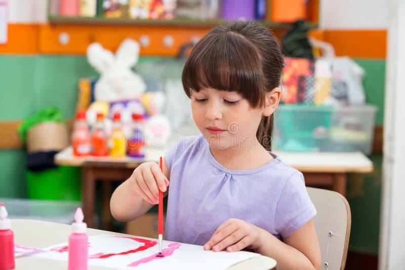 Peinture de fille au bureau dans la salle de classe photo libre de droits