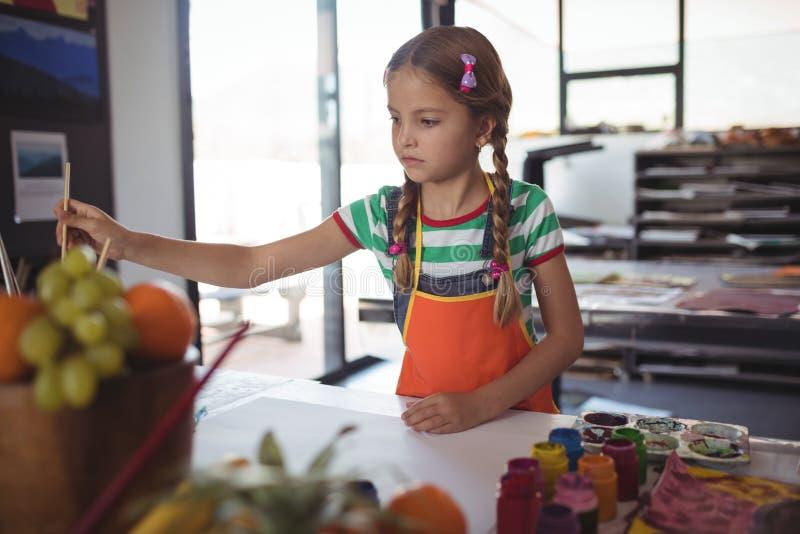 Peinture de fille au bureau dans la salle de classe image libre de droits