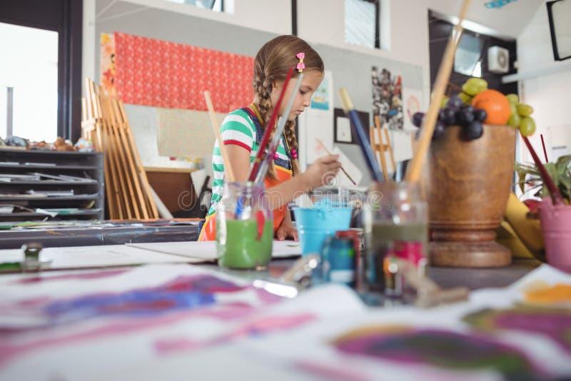 Peinture de fille dans la salle de classe photos stock