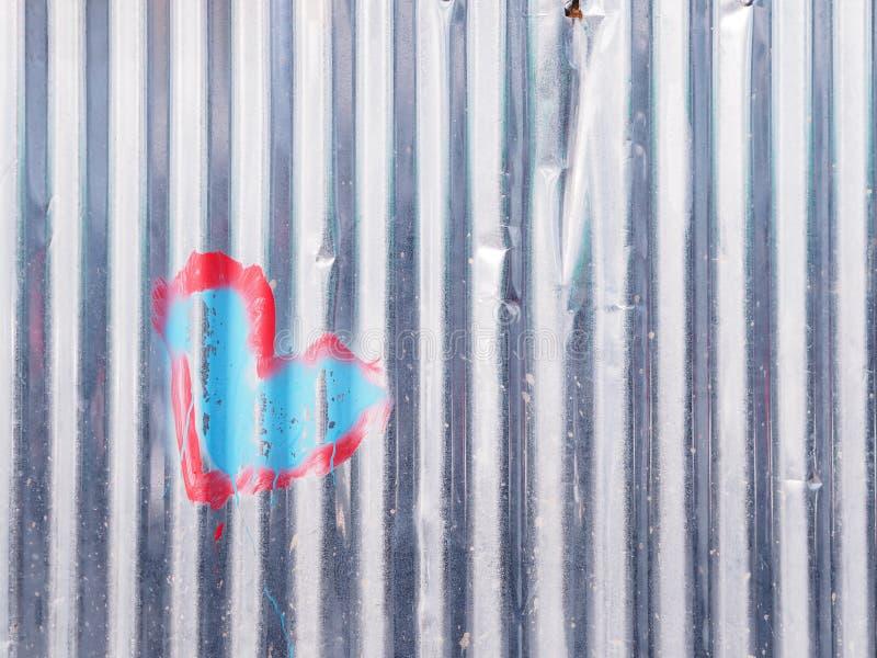 Peinture de forme de coeur sur le mur ondulé de zinc image libre de droits