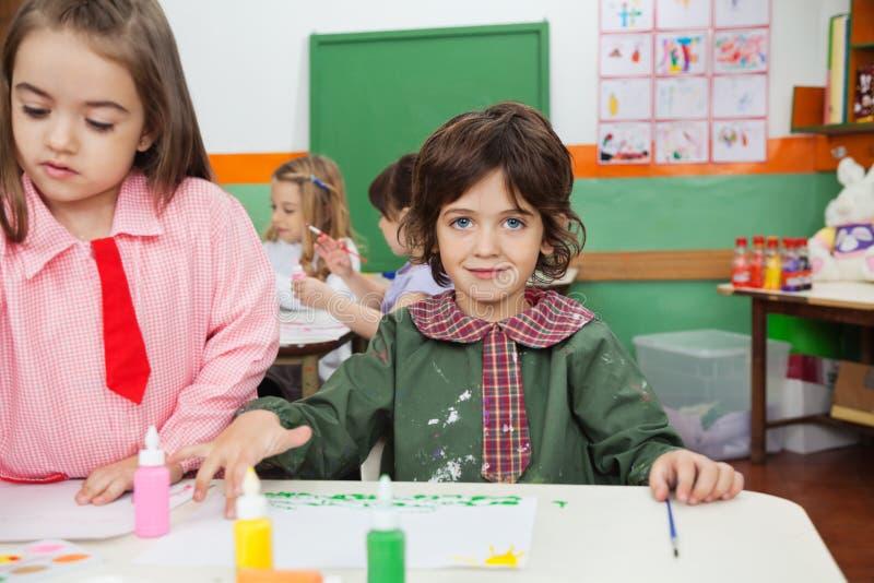 Peinture de garçon avec l'ami en Art Class image libre de droits