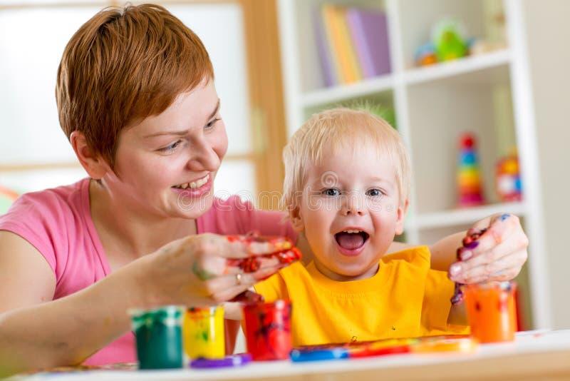 Peinture de garçon de mère et d'enfant en bas âge ensemble à la maison photos libres de droits