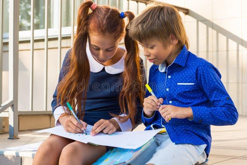 Peinture de garçon et de fille par des marqueurs près de l'école photographie stock libre de droits