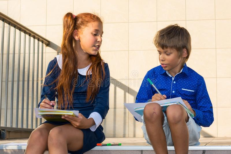 Peinture de garçon et de fille par des marqueurs près de l'école image stock