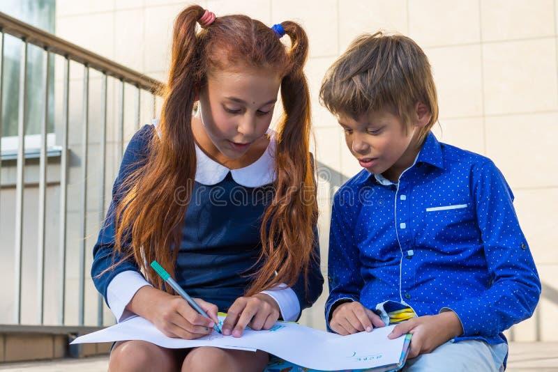 Peinture de garçon et de fille par des marqueurs près de l'école photos stock