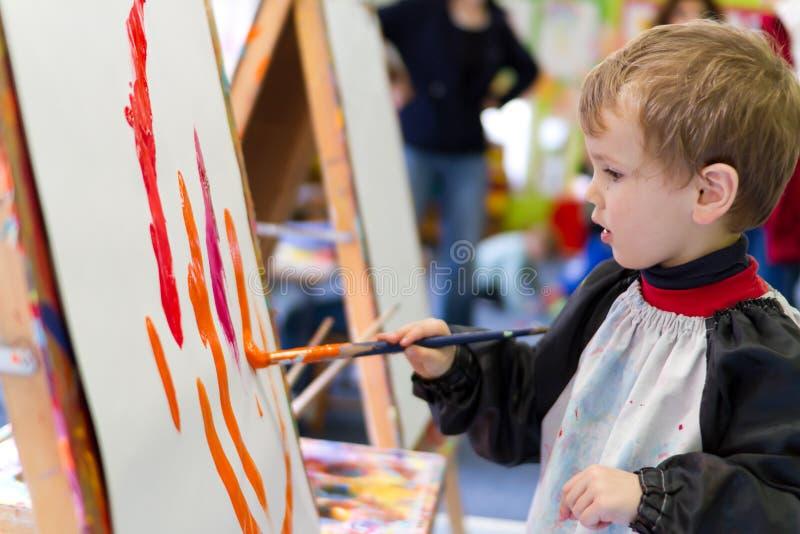 Peinture de gosse à l'école maternelle photo stock