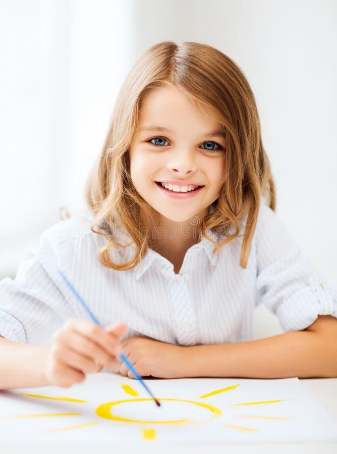 Peinture de petite fille à l'école image libre de droits