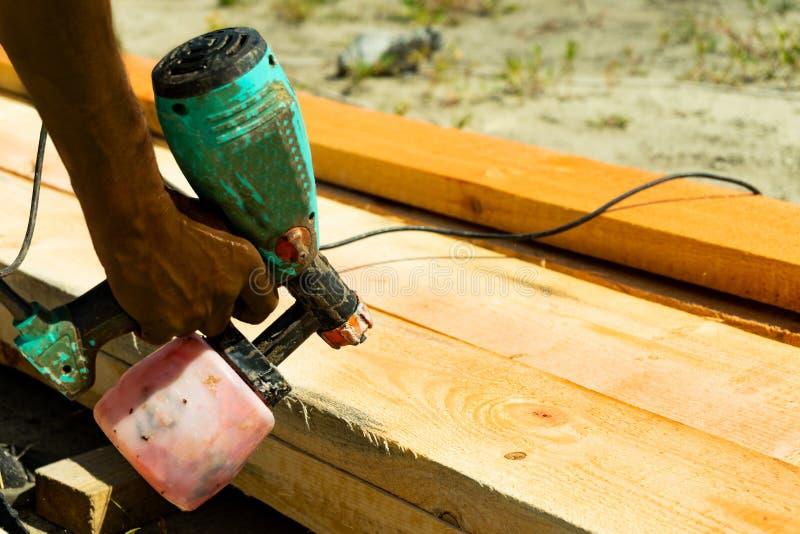 Peinture de pulvérisation de travailleur industriel au-dessus de bois de bois de construction Travailleur de la construction avec photographie stock