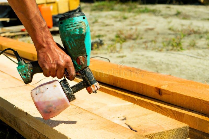 Peinture de pulvérisation de travailleur industriel au-dessus de bois de bois de construction Travailleur de la construction avec photos stock
