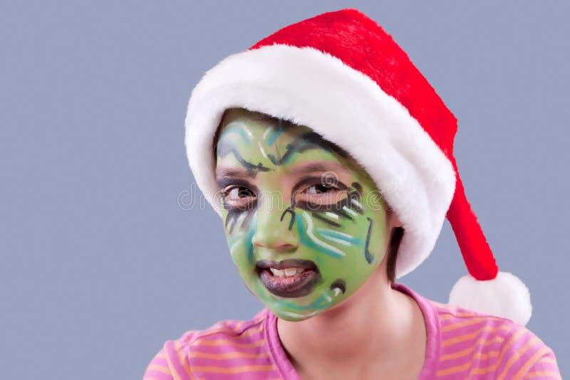 Peinture de visage et chapeau drôles de Santa. photographie stock libre de droits