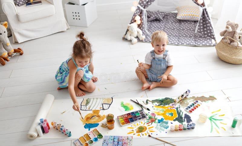Peinture drôle heureuse d'enfants avec la peinture photo libre de droits