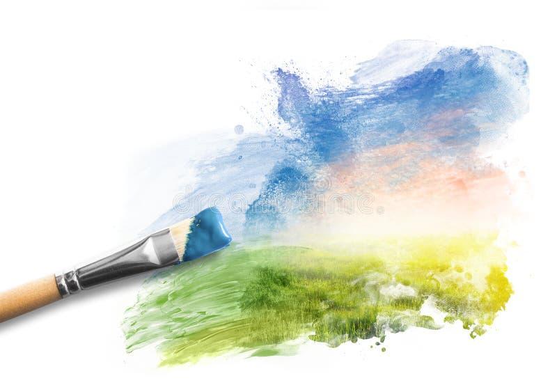 Peinture du paysage de ressort Brosse avec la peinture bleue au-dessus du ciel et du champ vert photographie stock libre de droits