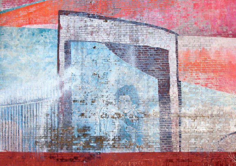 Peinture fanée d'art de rue d'un homme bleu sur un mur de briques photos stock
