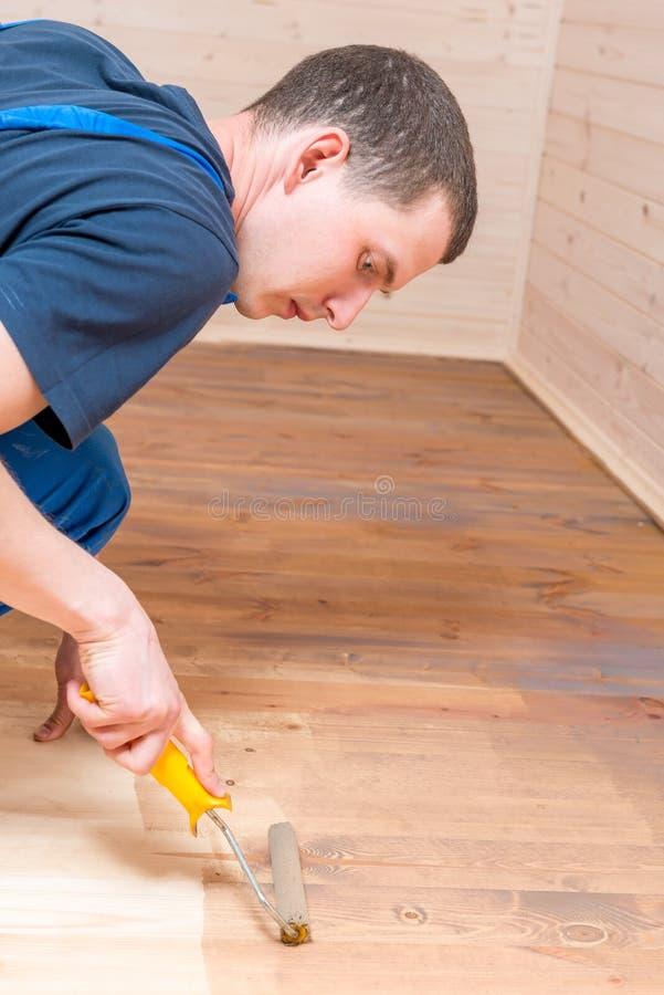 Peinture fonctionnante de rouleau sur un plancher en bois images libres de droits