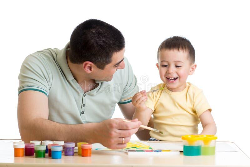 Peinture heureuse d'enfant en bas âge et de papa d'enfant d'isolement sur le blanc photo stock
