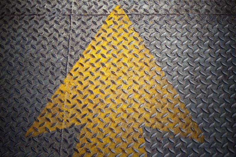 Peinture jaune de flèche sur l'acier photos stock