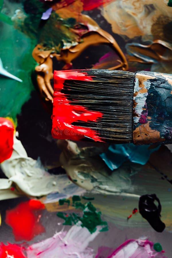 Peinture mélangée de brosse d'art sur la palette Outils de l'artiste à, souillés en encre après travail photographie stock libre de droits