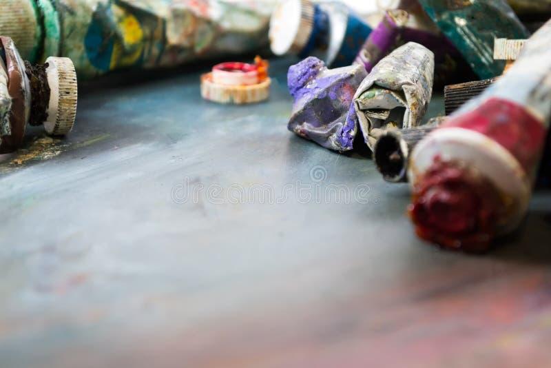 Peintures à l'huile lumineuses dans un tube sur une palette sale Peintures en service photo libre de droits