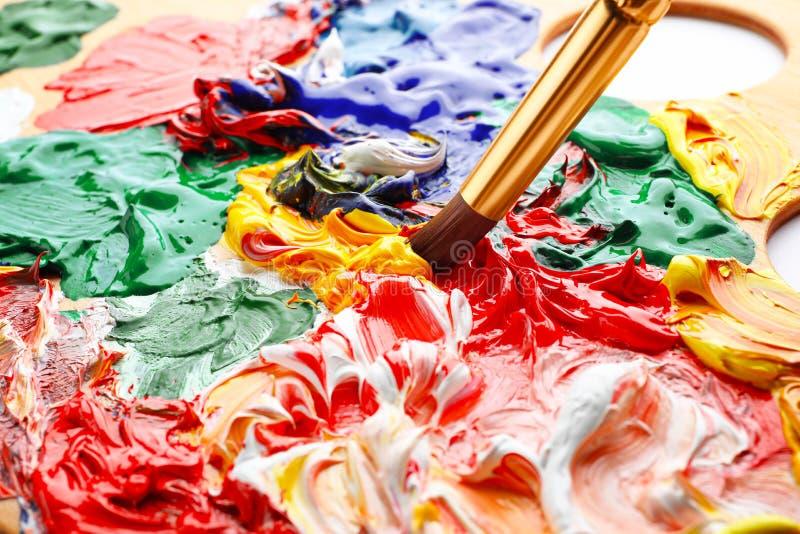 Peintures acryliques de mélange avec la brosse, plan rapproché photographie stock