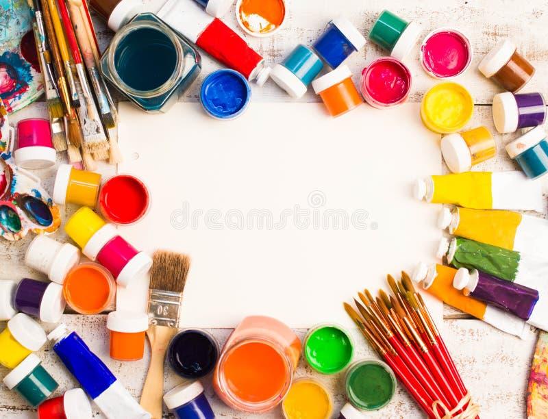 Peintures, brosses et palette sur le fond en bois blanc images stock
