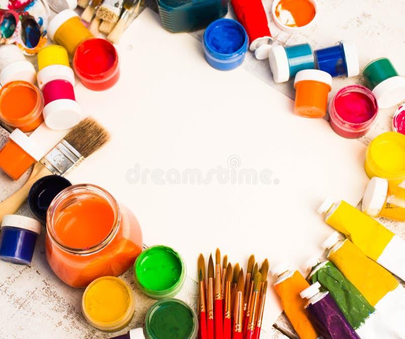 Peintures, brosses et palette sur le fond en bois blanc photo libre de droits