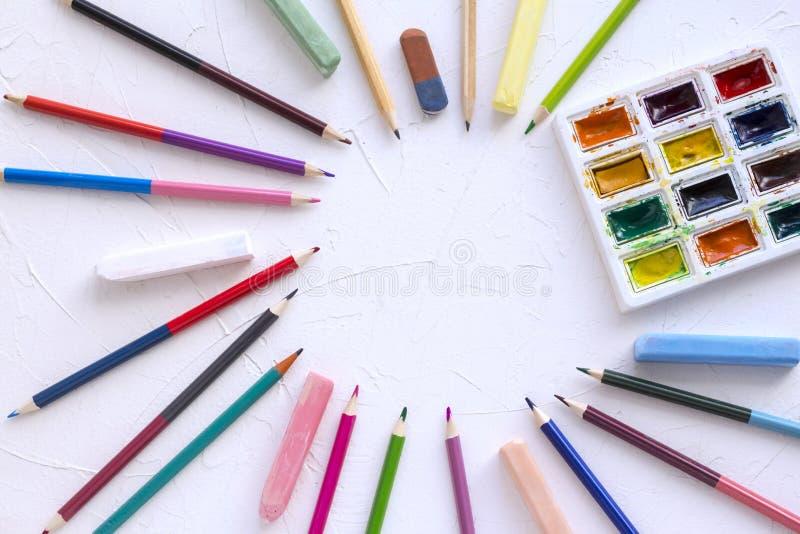 Peintures d'aquarelle pour dessiner et crayons avec la craie sur une table blanche Disposé en cercle image libre de droits