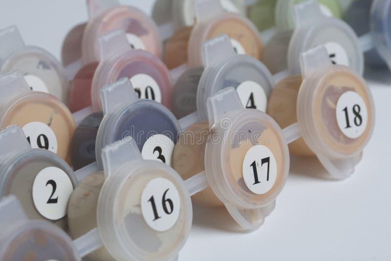 Peintures pour dessiner par des nombres Plusieurs récipients avec la peinture se situent dans une rangée photos libres de droits