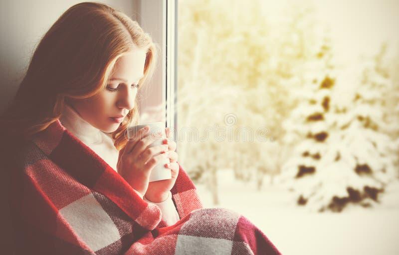 Peinzend droevig meisje met een verwarmende drank die uit binnen het venster kijken royalty-vrije stock fotografie