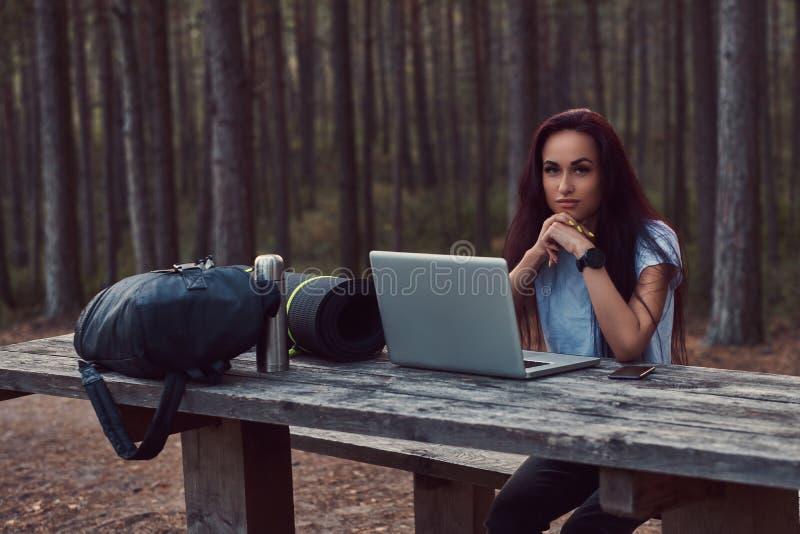 Peinzend hipstermeisje die in wit overhemd camera bekijken terwijl het zitten op een houten bank met open laptop in royalty-vrije stock afbeelding