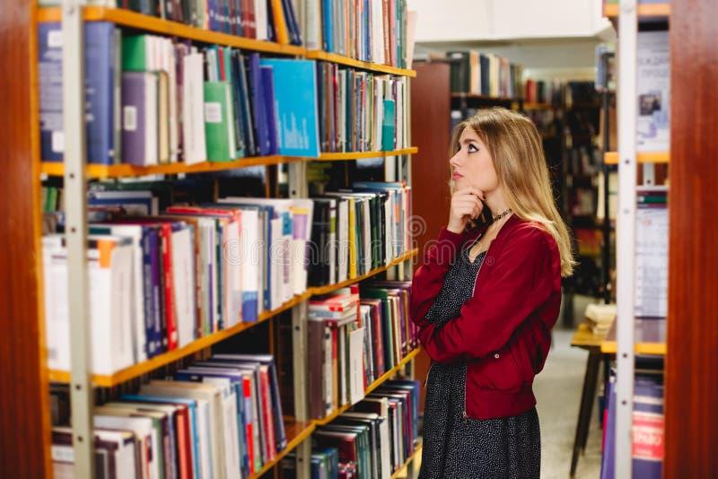 Peinzend meisje die een boek in universiteitsbibliotheek chosing Het concept van het onderwijs royalty-vrije stock foto