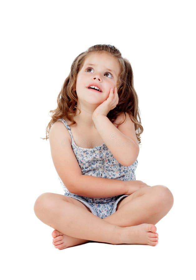 Peinzend meisje met drie éénjarigenzitting op de vloer stock afbeelding